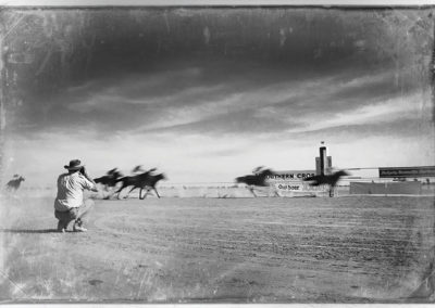 +Horses-gallop-past-the-finishing-post-during-the-Birdsville-Cup,-Queensland,-1989